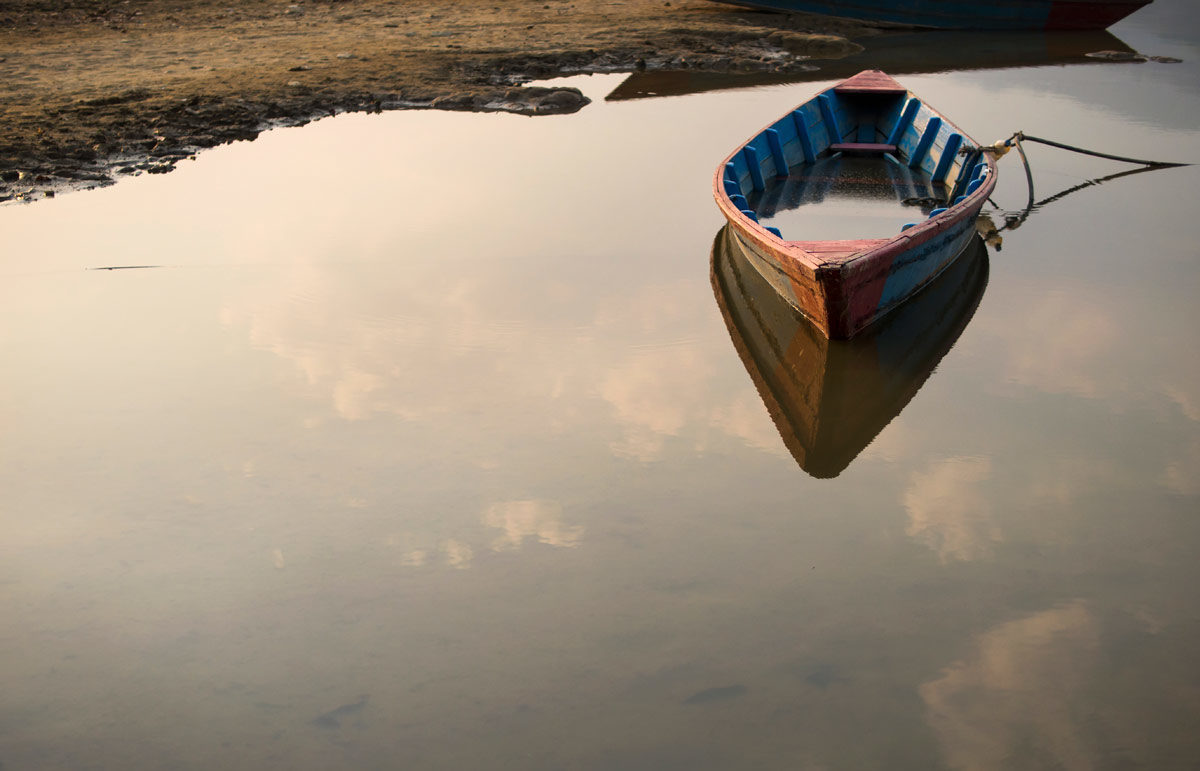 Photo of rowboat floating on still waters of a lake by rmnunes via iStock